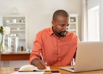 Mature man working on laptop while taking notes. Businessman working at home with computer while writing on agenda. African man managing home finance, reviewing bank account and using laptop in living room.
