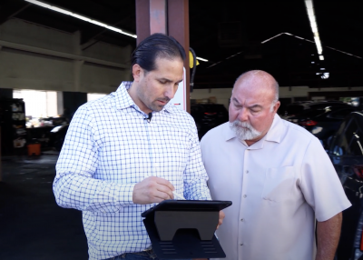 two men review FOG business inspection results on a tablet at an auto repair business