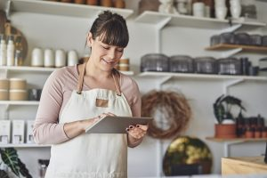 Smiling female business owner standing in her shop checking business license renewal status on tablet