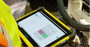 water utility mobile application shown in a tablet next to E.H. Wachs valve exercising machine