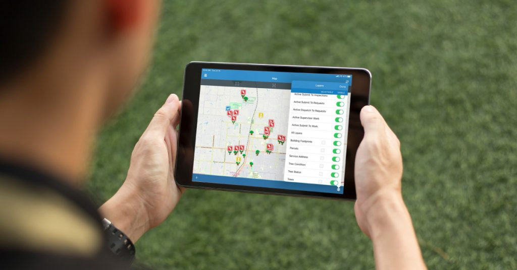 Man looks at tablet device displaying urban forestry map