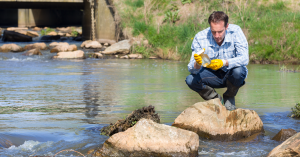 City employee collects water samples at river